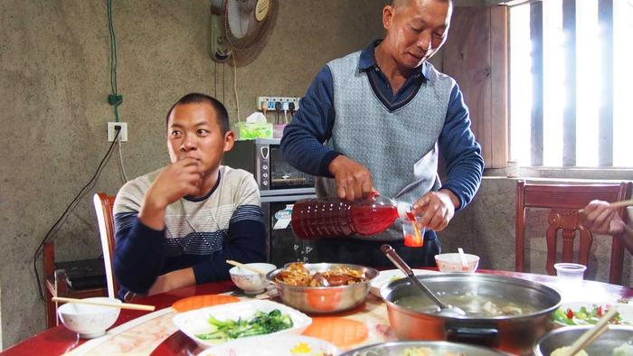 The Xie family serving moonshine and food to Arthur Tong.