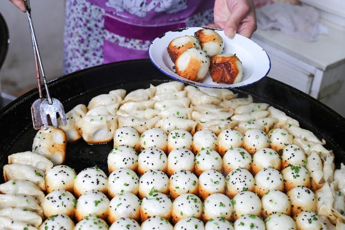 Shengjian are crammed tightly into a large pan to cook until their tops are steamed through and their bottoms pan-fried to a delicious crunch.