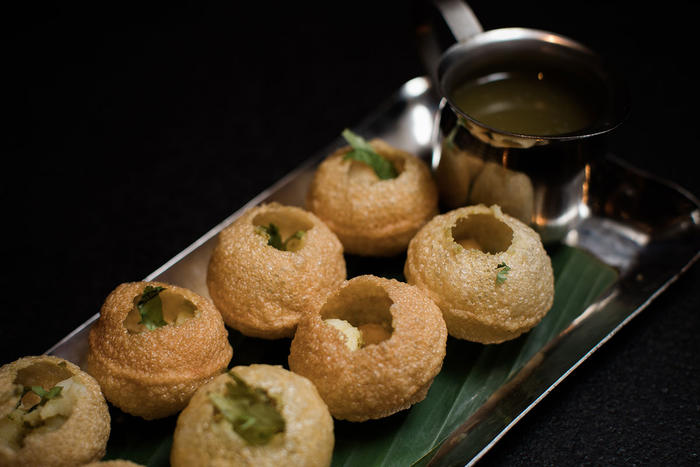 Pani puri are puffed up pastries stuffed with potatoes, chickpeas, coriander and mint.