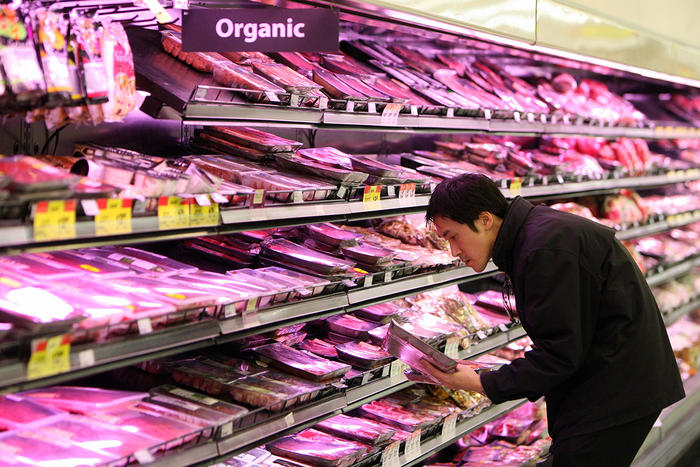 A customer selects meat products at a Woolworths supermarket