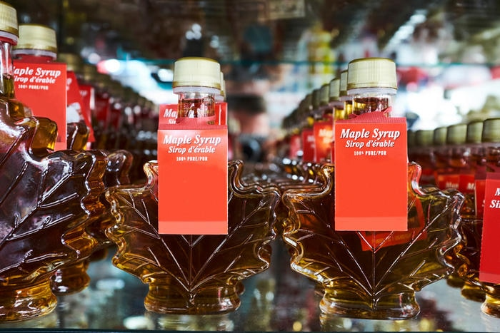 Rows of maple leaf shaped bottles containing maple syrup on shop shelf, Canada