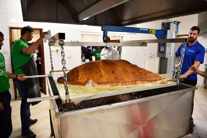 Muslim Aid staff work as they attempt to cook the world's largest samosa at the East London Mosque in London on August 22, 2017.