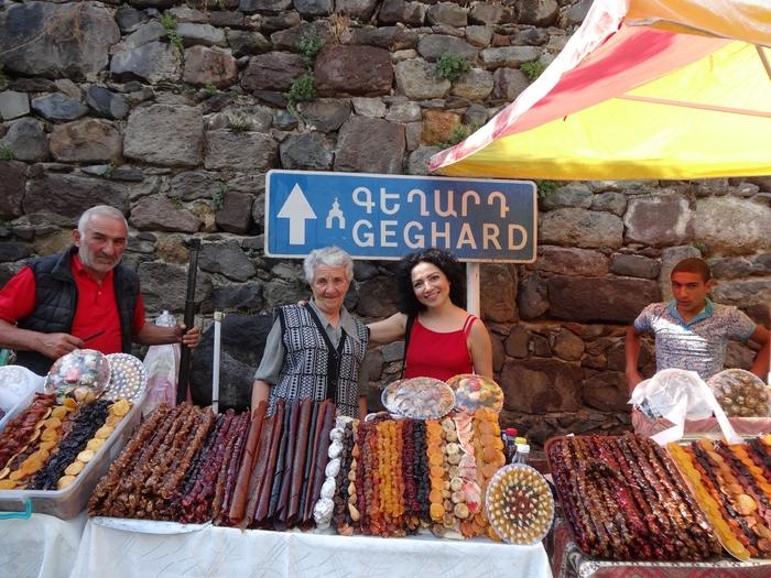 Arpy Iskikian, a caterer and cook from Sydney's Armenian community, poses with women selling Armenian delicacies near Geghard