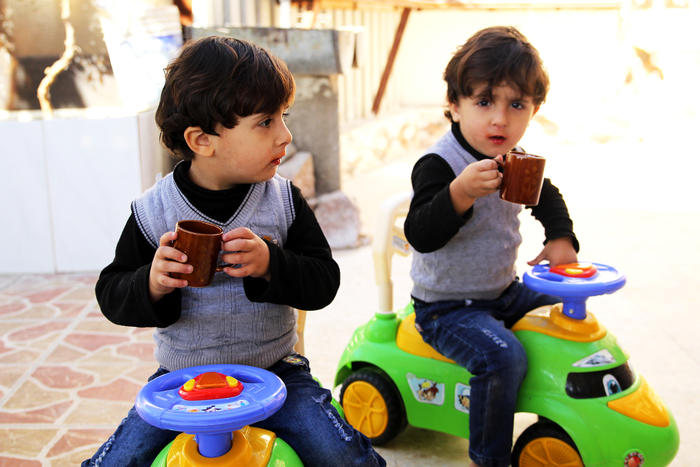 Shaldan's twin grandsons share a drink in the courtyard.