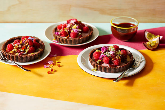 Raw raspberry, ginger and chocolate tarts with passionfruit and dark chocolate sauce