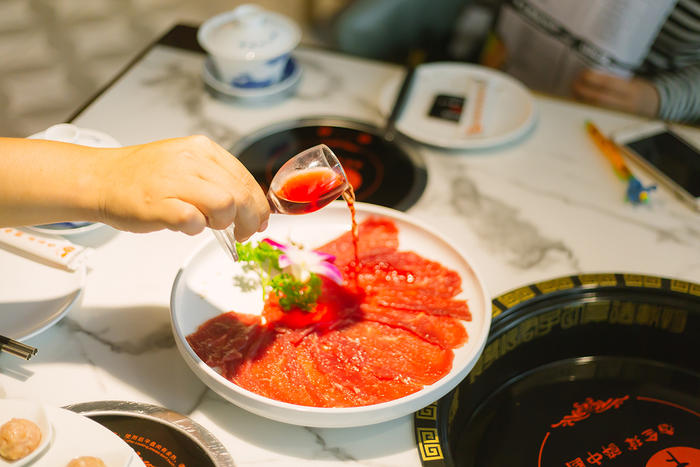 Red wine beef is one popular hotpot option with sides  and sauces - optional. (Ryan La)