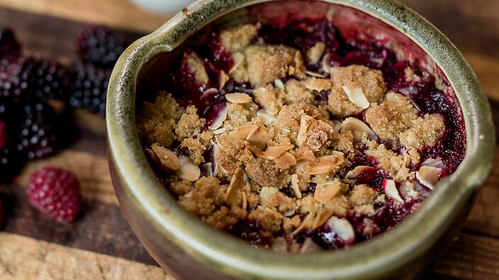 Rhubarb and berry crumble with goat's milk and vanilla custard
