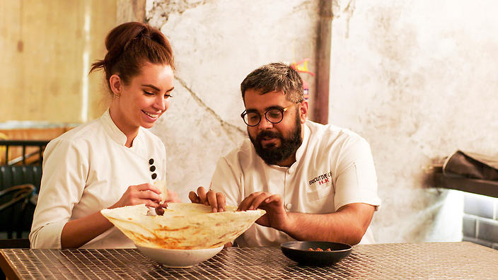Sarah Todd and Himanil Khosla eat roti