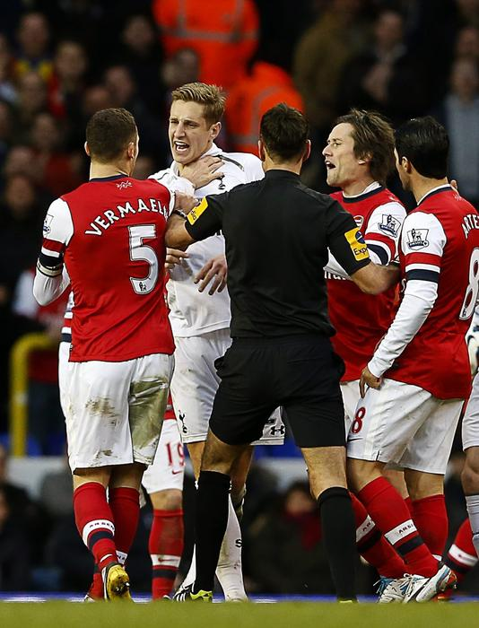 Michael Dawson of Tottenham Hotspur (2nd L) argues with Thomas Vermaelen of Arsenal (L) during a Premier League match in 2013.
