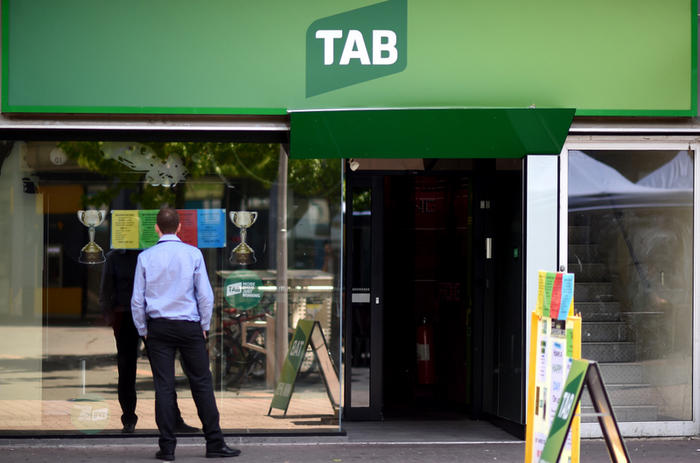 A man stands in front of a TAB betting branch in Canberra, Monday, Nov. 2, 2015. (AAP Image/Lukas Coch) NO ARCHIVING