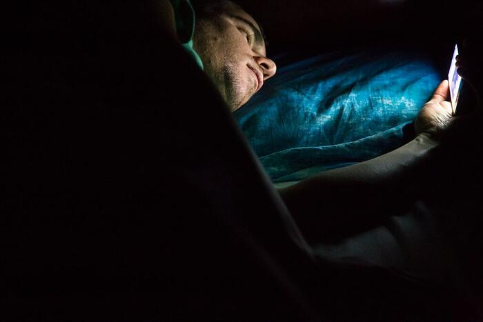 Man laying on bed at late night in a dark room checking his smartphone.