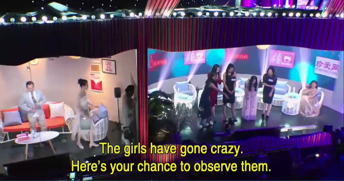 Contestants from 'Chinese Dating With the Parents' watching a potential suitor from a hidden room