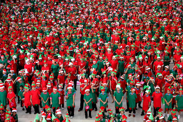 People dressed up as Santa's Elves line up during a photo-