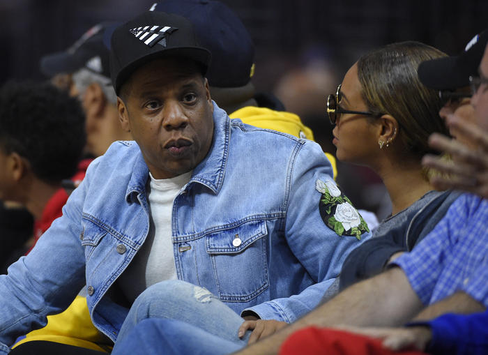 Singers Jay Z, left, and Beyonce watch during the first half of an NBA basketball game between the Los Angeles Clippers and the Brooklyn Nets, Monday, Feb. 29, 2016, in Los Angeles. (AP Photo/Mark J. Terrill)