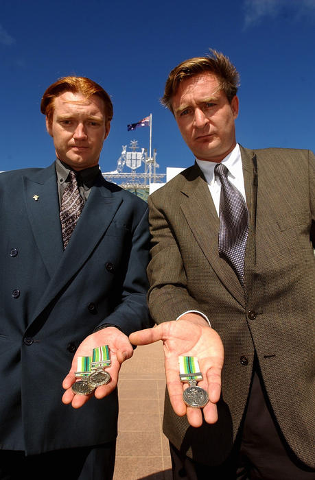 Canberra, March 20, 2003.  1991 Gulf war veterans Brett Jones (L) & Magnus Mansie display their medals before they returned them in opposition to a war against Iraq in Canberra today. They served on HMAS Success.  (AAP Image/Alan Porritt) NO ARCHIVING