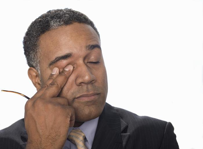 Businessman rubbing his eye