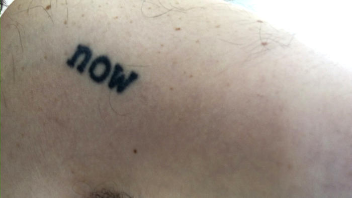 The author's tattoo of the word 'now'