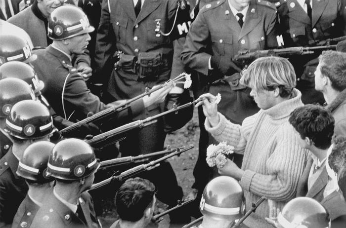 An antiwar demonstrator places flowers into the barrels of rifles while blocking the Pentagon on Oct. 21, 1967.