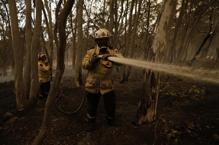 Members of the Sutherland Strike Force RFS contain a spot fire on a property in Colinton.