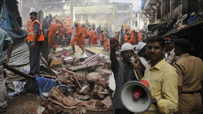 A rescue worker makes an announcement on a loudspeaker at the site of a building collapse in Mumbai India Thursday Aug. 31 2017