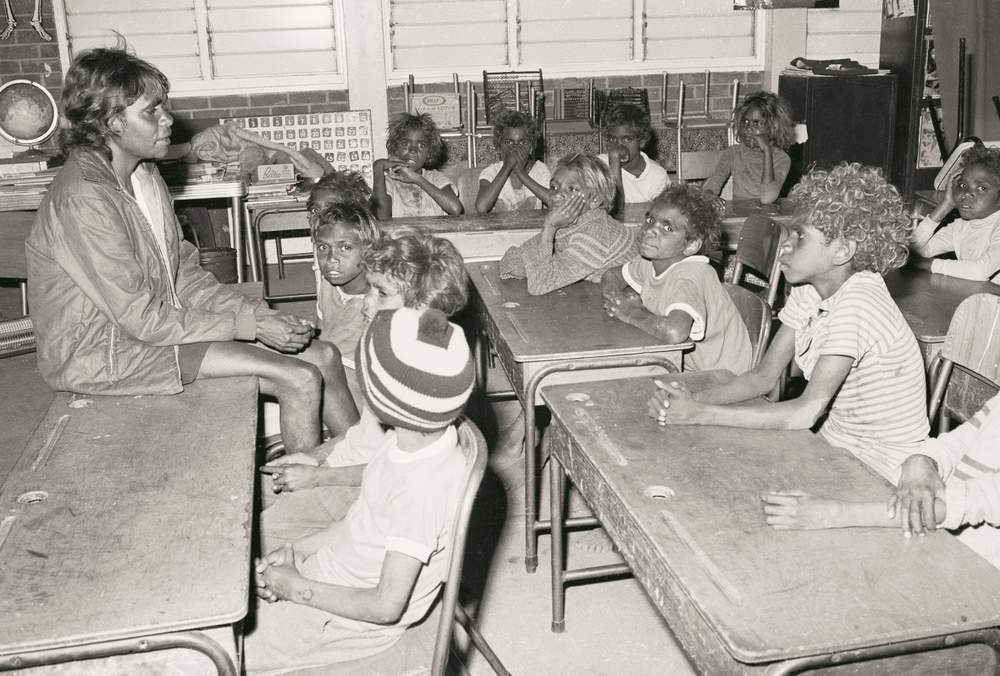 Tess Ross teaching a class Yuendumu School, 1964, with Francis Kelly (wearing the beanie) in the front row. (Image: Nation Archives Australia: A8739\/1, 11645325)