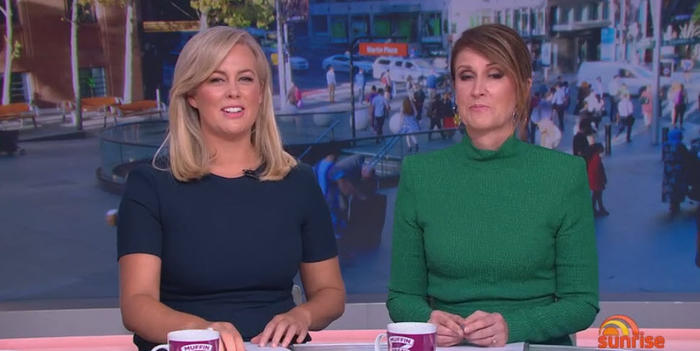 Sunrise presenters Sam Armytage and Natalie Barr put on a face as the show runs old overlay behind them to conceal a protest taking place earlier this morning.