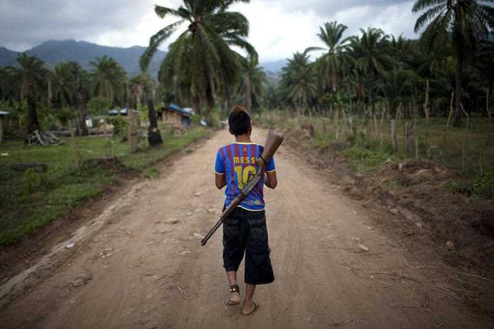 In this May 5, 2012 photo, Enrique Martinez, 17, with a rifle slung over his back, patrols an area of La Confianza, Honduras, a city developed from land seized by small-scale farmers from one of Honduras' richest men.