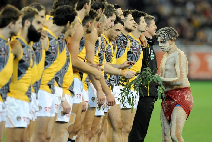 """Players are offered leaves as part of the """"Dreamtime at the G"""" ceremony before the match"""
