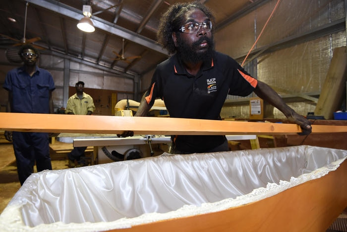 Supervisor Jason Wanambi inspects a coffin as part of the CDP launch
