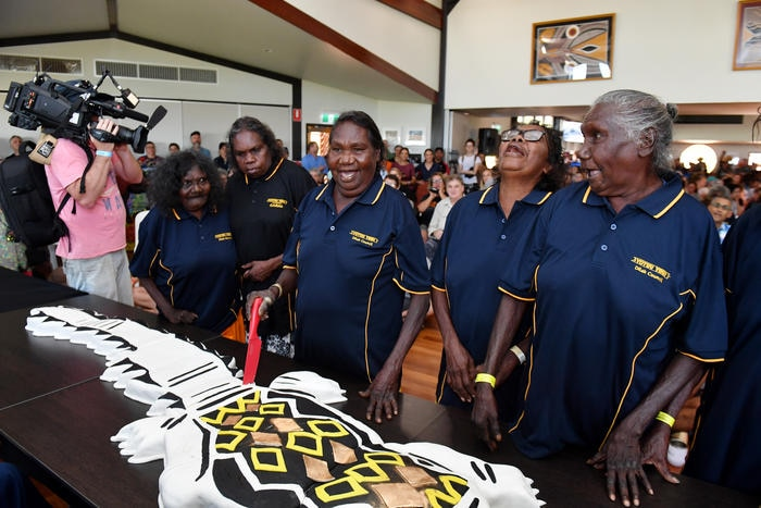 Local Yolngu women elders celebrate as they cut a cake to commemorate the 20th anniversary of the Garma Festival. (AAP Image/Mick Tsikas)