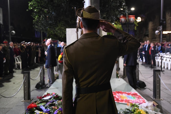 A flag bearer salutes during the Anzac Day Dawn Service at The Cenotaph in Sydney, Thursday, April 25, 2019. (AAP Image/Dean Lewins) NO ARCHIVING