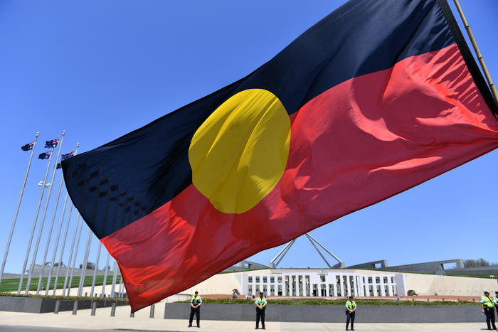 A marcher holds a flag as he protests for Aboriginal rights on Australia Day at Parliament House in Canberra, Sunday, January 26, 2020. (AAP)
