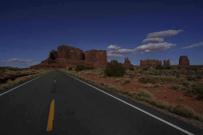 This April 23, 2020 photo shows an empty Interstate 163 in Oljato-Monument Valley, Utah, on the Navajo reservation. To help prevent the spread of COVID-19, the Navajo Monument Vally Tribal Park is closed. (AP Photo/Carolyn Kaster)