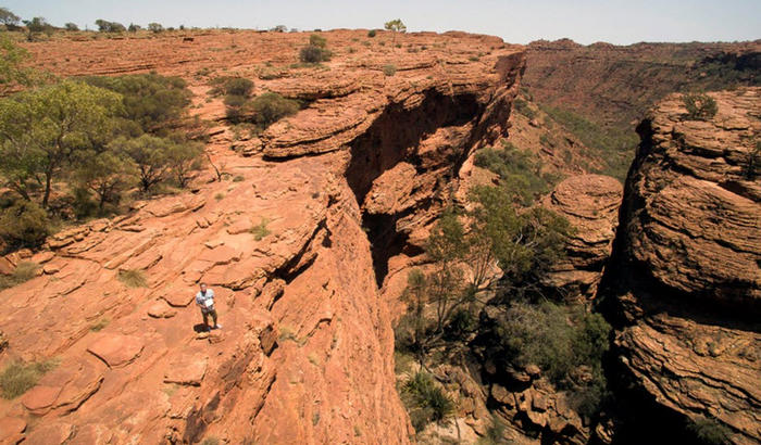 Photographer Andrew Gregory stands above the Garden of Eden at Kings Canyon in Watarrka National Park; he is preparing to fly his UAV copter through the narrow gap and up against the sheer canyon walls. The Garden of Eden penetrates into the water table a