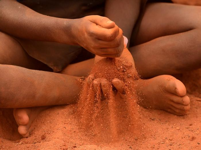 An indigenous child plays in red sand