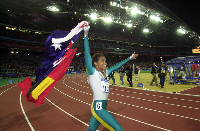 Cathy Freeman walks a lap of honour, carrying the Australian and Aboriginal Flags, after winning Gold in the Womens 400m Finals. (AAP PHOTO/Dean Lewins).
