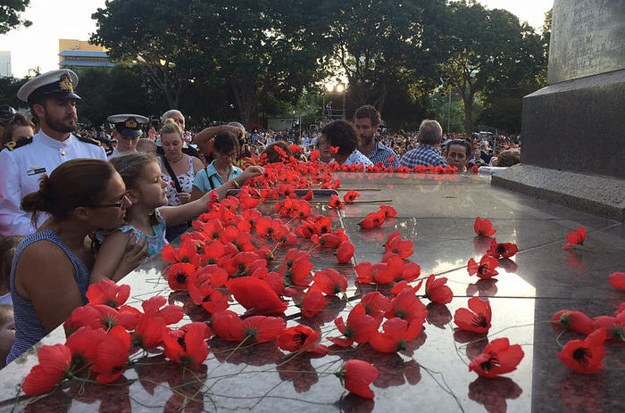 A young girl lays a poppy on the Darwin cenotaph following the Anzac Day dawn service at the Bicentennial Park in Darwin, Saturday, April 25, 2015.