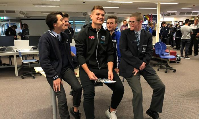 Port Adelaide Player Ambassador Ollie Wines with students as part of the Power to End Violence Against Women program.