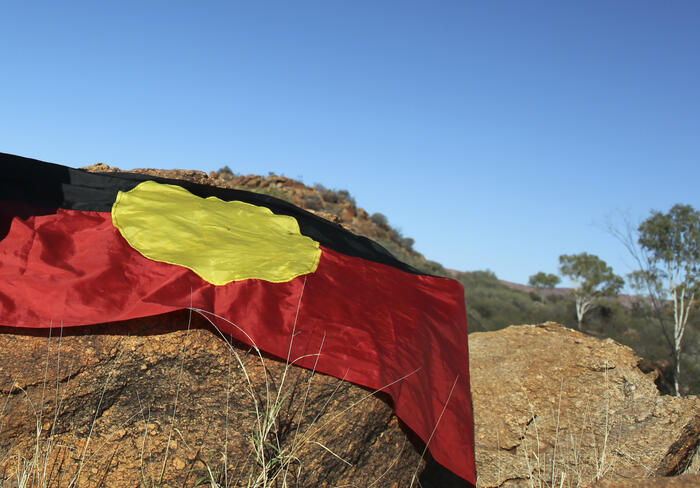 An Aboriginal flag on a rock in the outback.