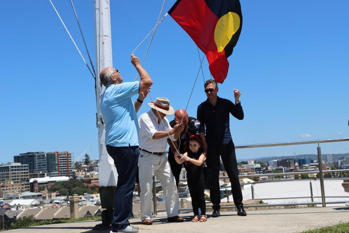 Isla Johnson helps raise the Aboriginal flag at Fort Scratchley for the first time.