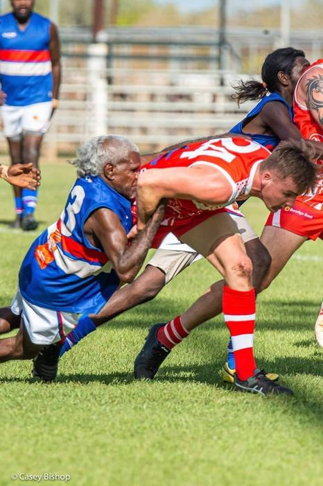 Keith Rogers cops an elbow to the face as he lays a tackle during a match at Nitmiluk Oval.