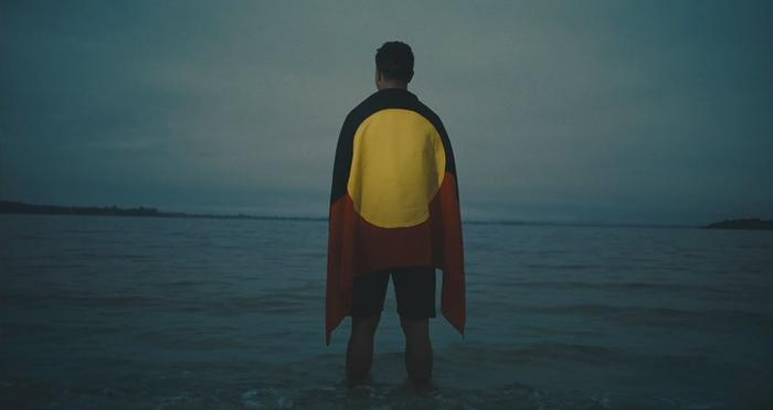 Latrell Mitchell clip from NRL advertisement 2020 draped in Aboriginal flag