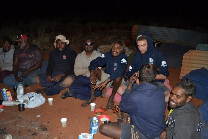 The men enjoy a hot meal and a cup of tea as they share a yarn around a warm camp fire.