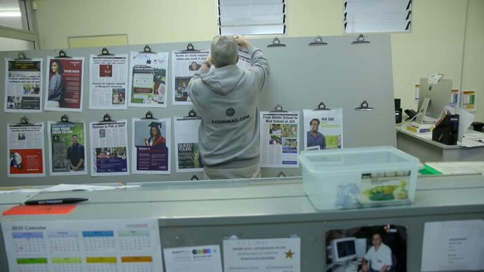 Koori Mail staff member Stuart Corlett hangs up the pages ready for printing