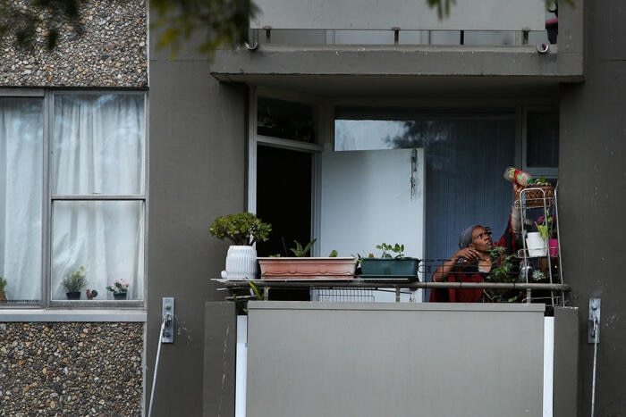 A resident tends to plants on a balcony of a public housing apartment in Redfern on 16 September 2021 (Lisa Williams/Getty).