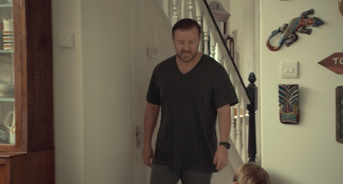 Ricky Gervais's character in Netflix series 'After Life' walks past a dot painted souvenir on the wall.