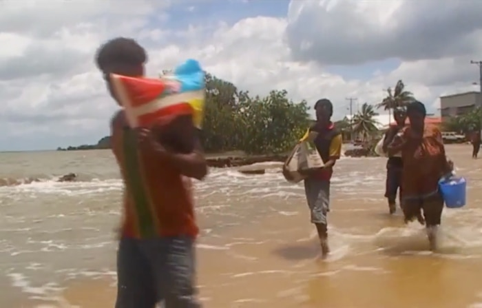 Torres strait Islanders carry supplies as a high tide washing over a sea-wall and into the community.