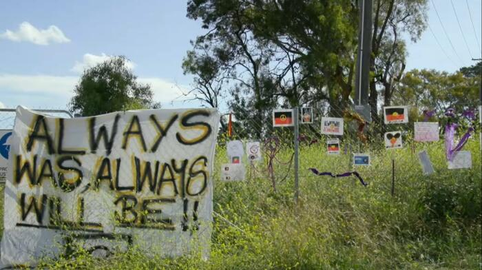 Signs of protest and solidarity on the fence of the proposed go-kart track site.