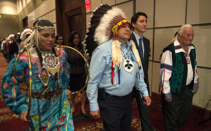 Aboriginal dancers and elders walk with Canada's Prime Minister Justin Trudeau and AFN National Chief Perry Bellegarde as they enter the hall at the Assembly of First Nations Special Chiefs Assembly in Gatineau, Quebec
