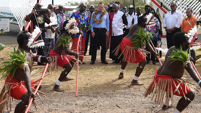 Prime minister Tony Abbott is given a traditional welcome as he arrives to visit the grave of land rights activist Eddie Mabo on Mer Island in the Torres Strait (AAP)